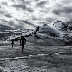 Brendan and Kris jogging on the dry Sentinel Glacier with the N Face of Nch'Kay and Dalton Dome in the background.